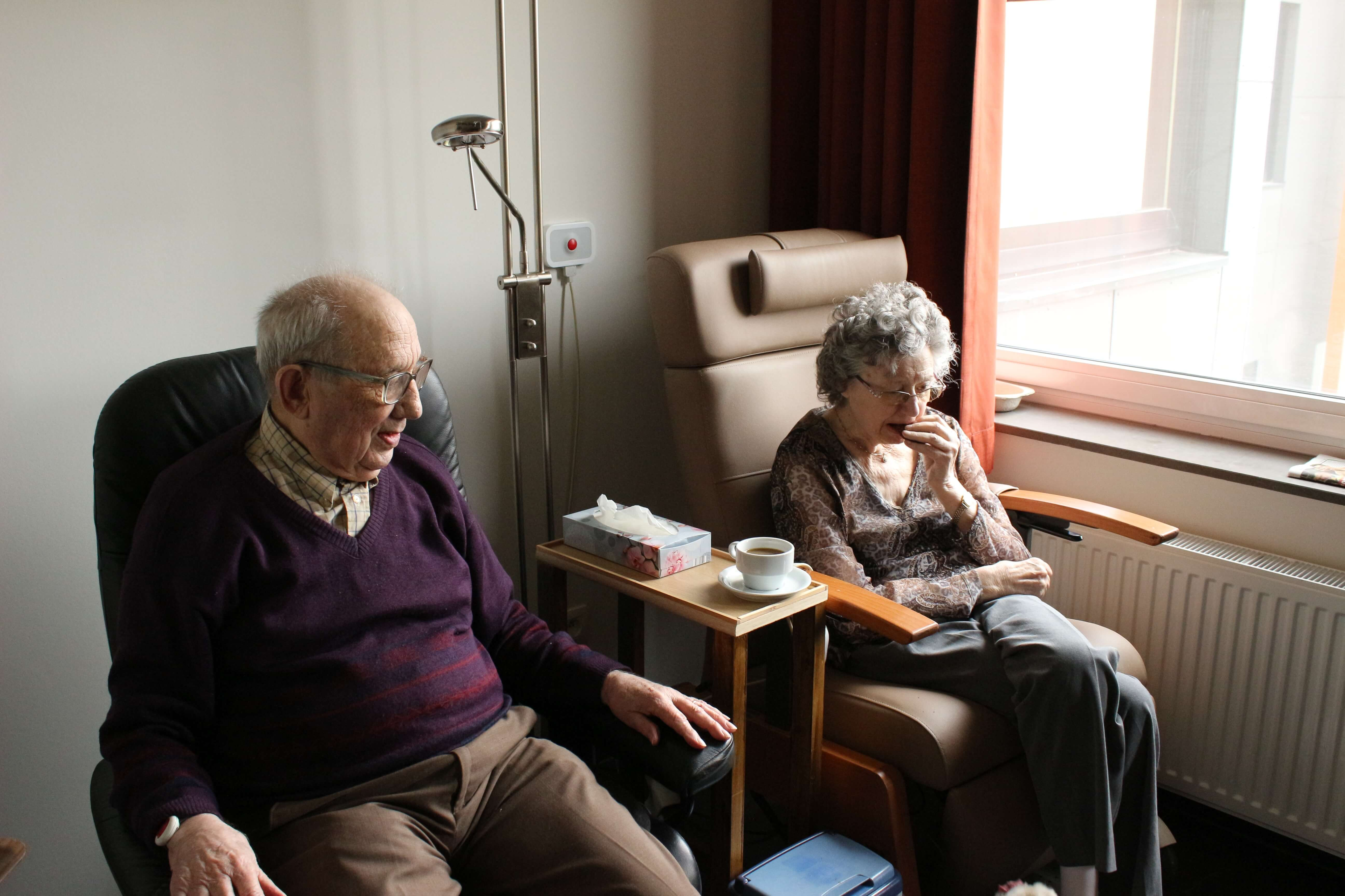 An elderly couple relax in an assisted living residence, sitting next to each other on high-backed chairs next to a window.