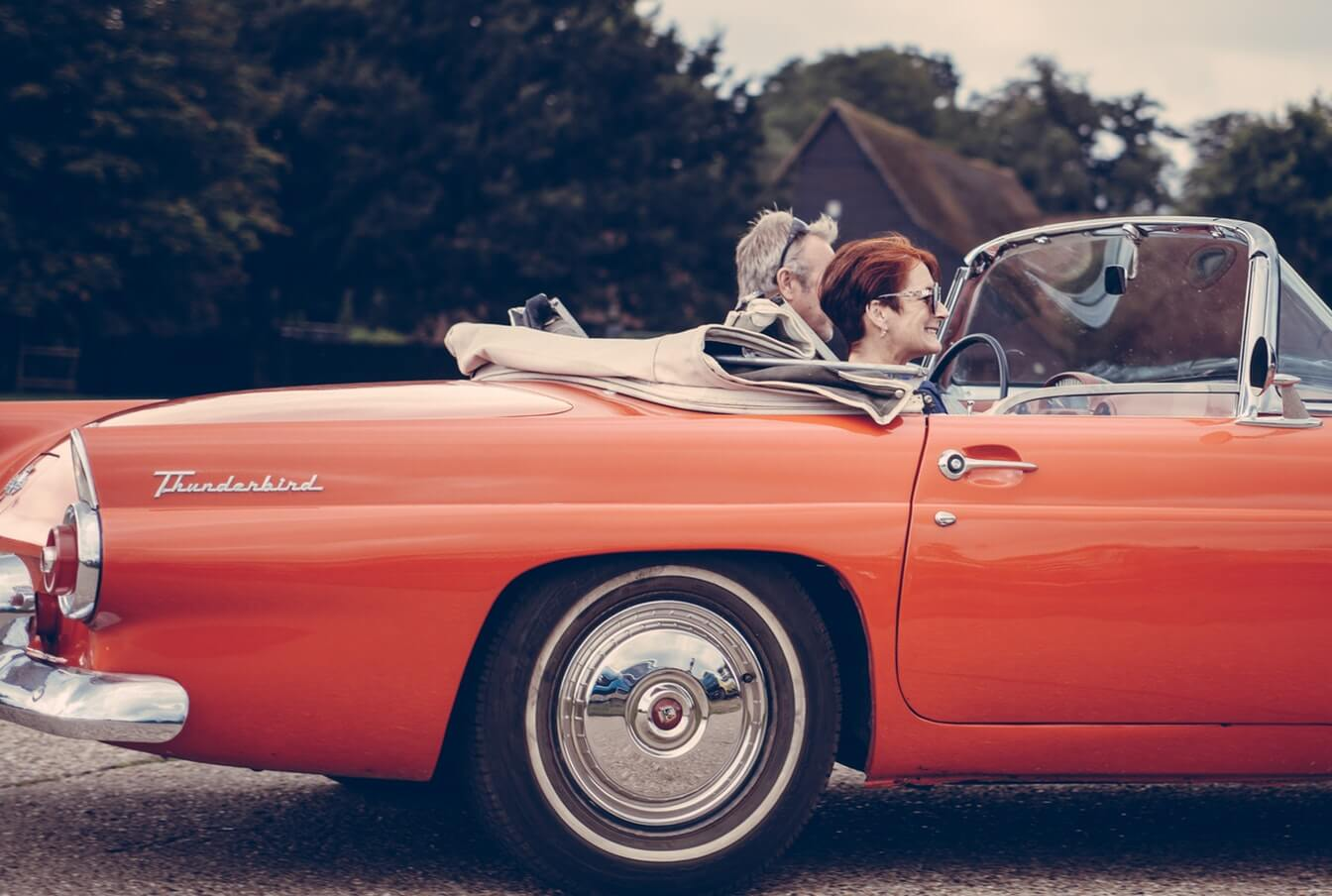 A retired couple smile as they drive in a vintage convertible Thunderbird.