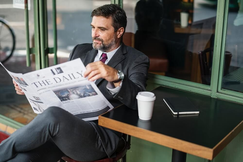 CEO in his late fifties reads the daily paper