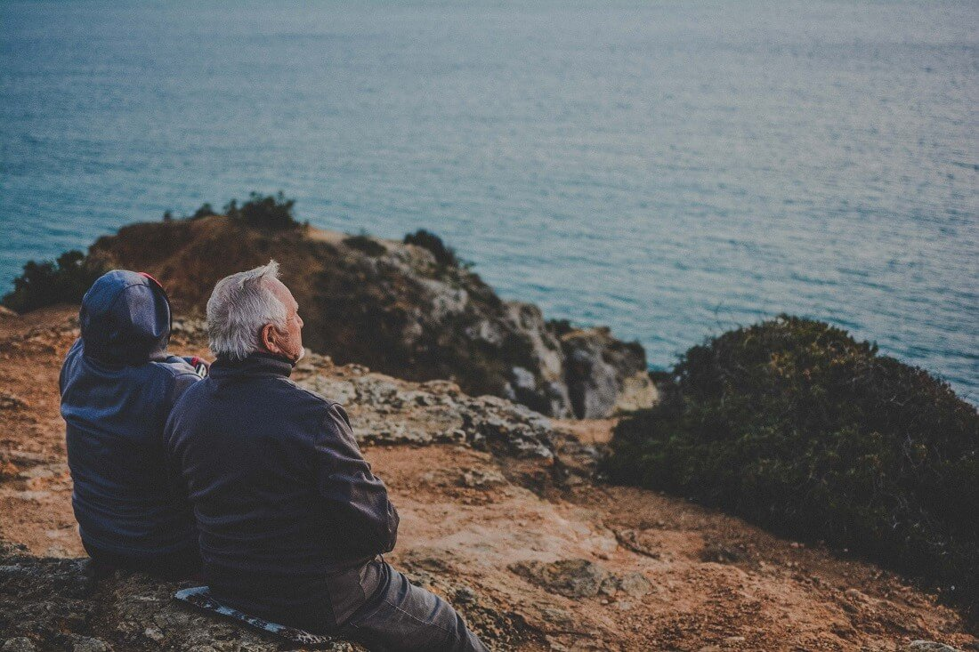 An elderly couple sits on top of a hill overlooking the ocean