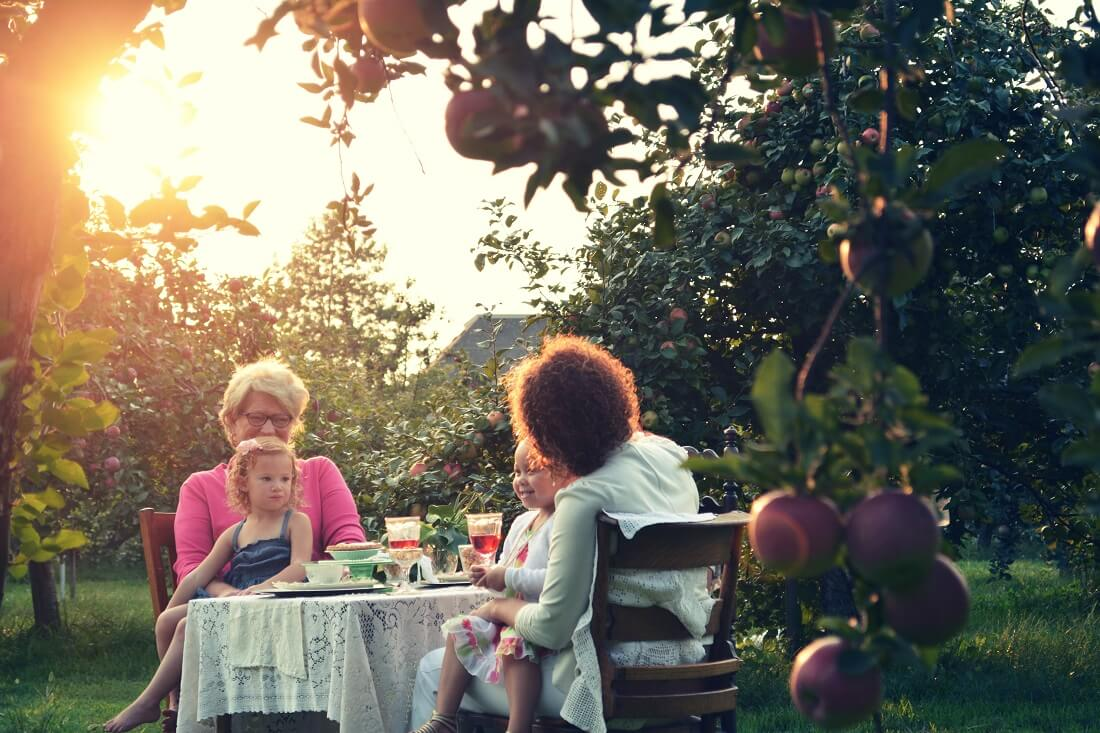two senior woman with their young grandchildren having lunch outdoors