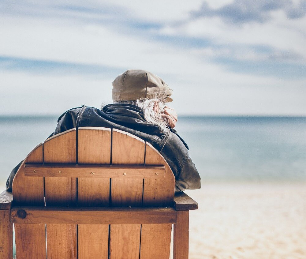 Old man sits in an adirondack chair looking at the beach